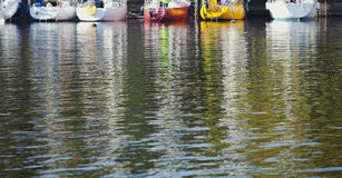 Reflection of boats in green river water Stock Images