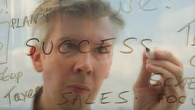 Reflection of a brainstorming businessman writing business words onto glass. Reflection of a brainstorming businessman brainstorming planning a solution writing stock video footage
