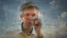 Reflection of a brainstorming businessman writing business words onto glass. Reflection of a brainstorming businessman brainstorming planning a solution writing stock footage