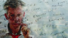 Reflection of a brainstorming businessman writing business words onto glass. Reflection of a brainstorming businessman writing business keywords onto glass with stock video footage