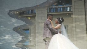 The reflection of bride and groom in a puddle. Lovely bride and groom with puddle water ground reflection. Newlyweds talking while photo shooting. Happy marriage stock video footage