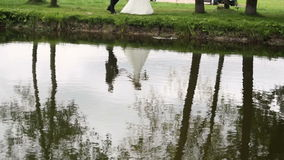 Reflection of the bride and groom in the water stock footage