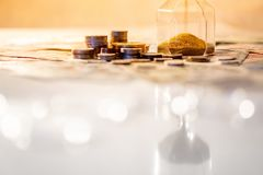 Reflection of hourglass with currency on glowing table. Reflection of brown sand running through the shape of modern hourglass on glowing table with currency Stock Photos