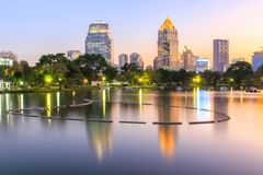 Reflection business district building from a park with night scene from Lumpini Park. Bangkok, Thailand royalty free stock images