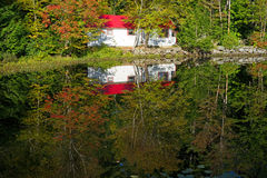Reflection of camp on pond. A reflection of a small camp on a pond with the autumn leaves in Northern Maine Stock Images