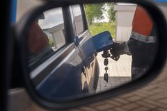 Reflection in car mirror of the man fuel the car on petrol station.  stock image