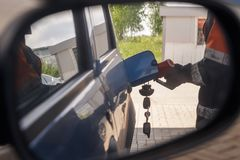 Reflection in car mirror of the man fuel the car on petrol station.  stock photos