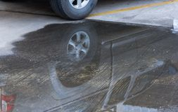 Reflection of the car. In a puddle of water on the cement floor Royalty Free Stock Image