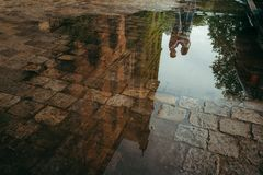 The reflection of the charming hugging couple in the puddle. Poland location. The reflection of the charming hugging couple in the puddle. Poland location Stock Photos