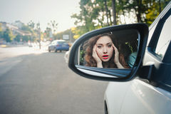Reflection of a cheerful beautiful girl in a side mirror of a car Royalty Free Stock Image