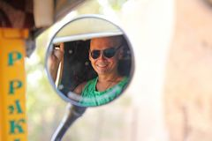 Reflection in a circular mirror. The male face is reflected in the mirror of the tuk tuk. A tourist man in sunglasses is reflected royalty free stock image