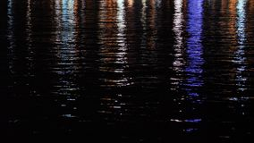 Reflection of city lights in the water at night. stock video footage