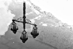 Reflection. Classic lantern reflected in the early morning rain in Italy Stock Photo