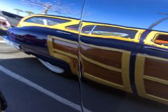 Reflection of a Packard Woody. The reflection of a classic Packard Woody on the surface of another car. Seen at Cars & Coffee Folsom, California Royalty Free Stock Photography