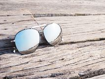 Reflection in sunglasses on wood background. Reflection of clear blue sky in fashionable mirror sunglasses on vintage wood background Royalty Free Stock Image