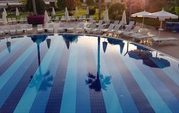 Beautiful reflection in clear water of blue swimming pool with chaise-longues in luxury resort hotel royalty free stock photography