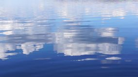 Reflection of clouds in blue water stock footage