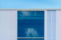Reflection of clouds in blue window Royalty Free Stock Images