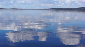 Reflection of clouds on lake surface stock video footage