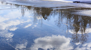 Reflection of clouds in puddle Stock Photos
