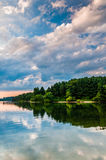 Reflection of clouds and trees in Lake Marburg, at Codorus State Royalty Free Stock Photo