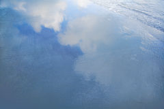 Reflection of clouds in waves at the beach Royalty Free Stock Image