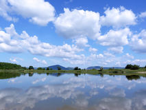 Reflection of the cloudy blue sky in the lake surface. In summer Stock Images