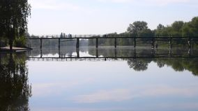 Reflection of cloudy blue sky on the surface of the river and Bridge over river. Landscape reflection of a cloudy blue sky on the surface of the river and bridge stock footage