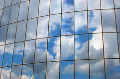 Reflection of a cloudy sky in glass wall Stock Images