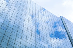 Reflection of a cloudy sky in glass wall Stock Image