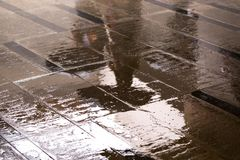 Reflection of people with umbrellas in a puddle on the granite floor in the underpass royalty free stock photos