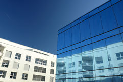 Reflection and contrast. A modern office block with blue glass facade reflects a more conventional building behind. A con-trail from an aircraft in the sky Royalty Free Stock Photography