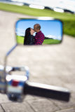 Reflection of couple kissing in motorbike motor Stock Photo