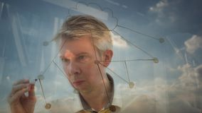 Reflection of a businessman drawing an image of a cloud network. Reflection of a creative businessman brainstorming drawing an image of a cloud network backlit stock footage