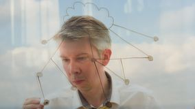Reflection of a businessman drawing an image of a cloud network. Reflection of a creative businessman brainstorming drawing an image of a cloud network with a stock footage