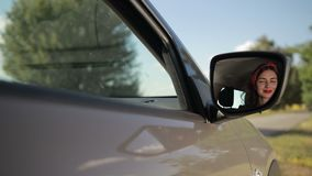 Reflection of cute girl in rearview mirror of car stock footage
