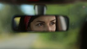 Reflection of cute woman in car rearview mirror stock video footage