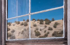 Reflection of desert in window of abandoned building, ghost town Chloride NM royalty free stock image