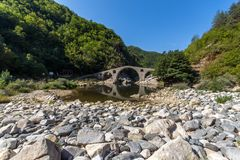 Reflection of Devil`s Bridge in Arda river and Rhodopes mountain, Kardzhali Region, Bulgaria Stock Photo