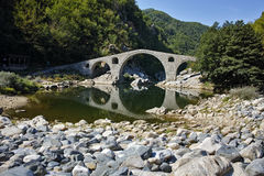 Reflection of Devil's Bridge and Rhodopes mountain in Arda river, Bulgaria Royalty Free Stock Photos