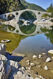 Reflection of The Devil's Bridge and Rhodopes mountain in Arda river, Bulgaria Royalty Free Stock Photos