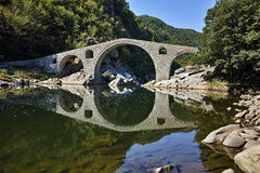 Reflection of The Devil's Bridge and Rhodopes mountain in Arda river, Bulgaria Royalty Free Stock Photography