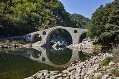 Reflection of Devil's Bridge and Rhodopes mountain in Arda river, Bulgaria Stock Photo
