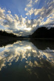 Reflection of dramatic clouds with sunrays royalty free stock images
