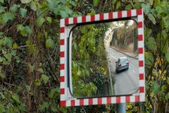 Reflection of a driving car in a mirror Stock Image