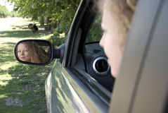 Reflection of driving woman in the mirror Stock Images