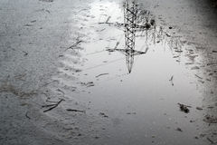 Reflection of an electricity pylon in a puddle. The reflection of an electricity pylon in a puddle on the road Stock Images