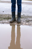 Reflection of feet in muddy boots a puddle Royalty Free Stock Photos