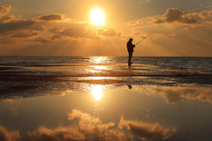 Reflection of a fisherman at dawn. Fisherman standing on a pier at dawn sky background with sun rays and reflected in the sea water Stock Photos