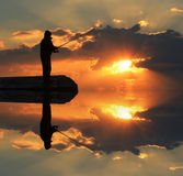 Reflection of a fisherman in the water. Stock Images